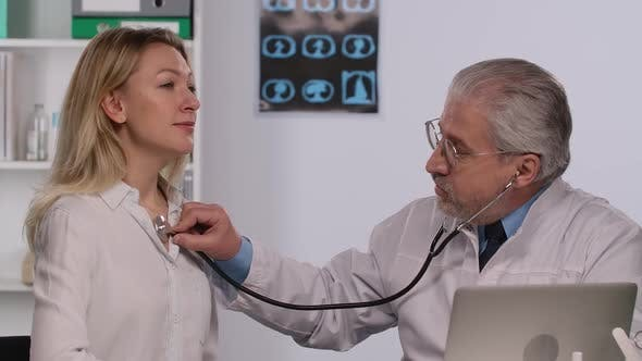 Family Medicine Doctor Examines a Woman Patient with a Stethoscope