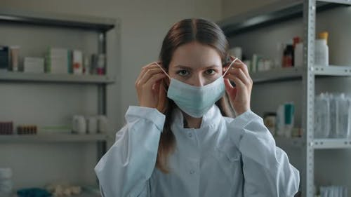 Pharmacist Woman Putting on Medical Mask at Drugstore