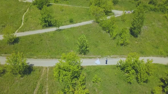 Thumbnail for Bride Spins Near Groom on Hairpin Curves of Path Upper View