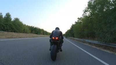 Biker is Accelerating at Motorcycle on Empty Country Road