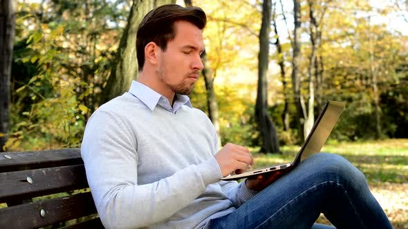 Thumbnail for Young Handsome Man Sitts on Bench in a Park and Works with a Laptop
