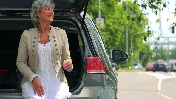 Thumbnail for Middle Aged Woman Sits in the Trunk and Looks Around - Street with Passing Cars in the Background