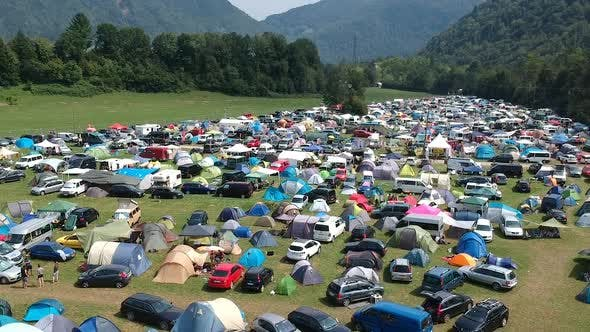 Thumbnail for Aerial drone shot of a camping ground at a music festival in a green and lush mountainous area.