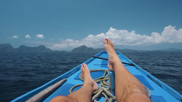Man Legs on Banca Boat Deck on Island Hopping Trip Approaching Tropical Island. Travel, Relaxation