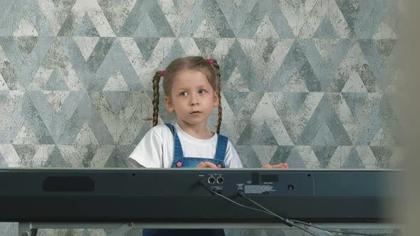 Girl with Long Pigtails Plays on Electronic Piano