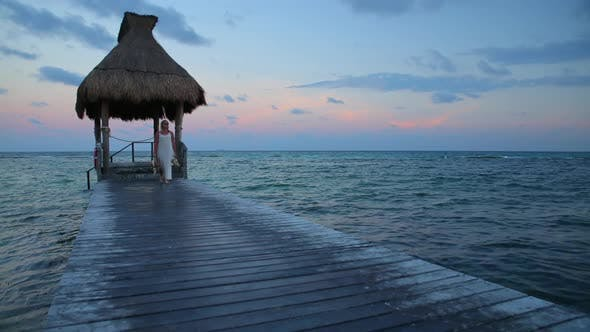 Thumbnail for Woman walks down pier at tropical resort