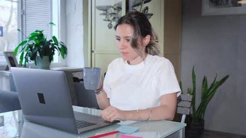 Attraktive junge Frau, die Spaß daran hat, was sie tut, während sie in ihrem schönen Computer arbeitet