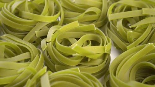 Dry green nest pasta tagliatelle close up