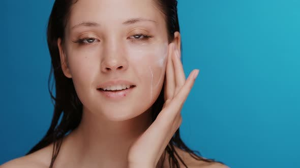 Thumbnail for Fresh and Beautiful Woman with Wet Hair Applying Cream on Cheek and Under Eye Zone Smiling To Camera
