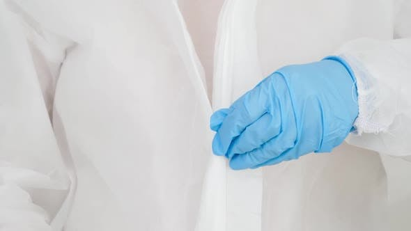 Closeup of Female Doctor Wearing and Zipping Protective Suit Against Viruses and Biohard
