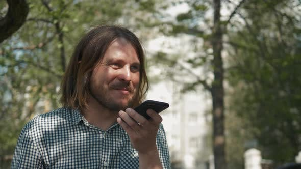 Cover Image for Hipster Man Sending Voice Messages with Mobile Phone at Park Audio Voice Recognition Ai Speech
