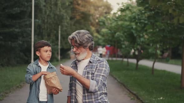 Thumbnail for Grandson and Grandfather Eating Snack in a Park