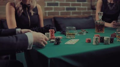 Man Mixes and Distributes a Deck of Cards. Company Plays Poker. Gaming Chips, Money, Cigars
