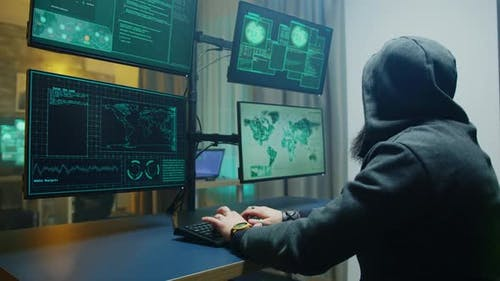 Side View of Masked Hacker Writing a Dangerous Malware