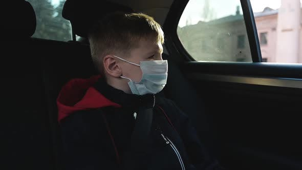 Thumbnail for Portrait Child Boy in Protective Face Mask Looks Out Moving Car Window on Street