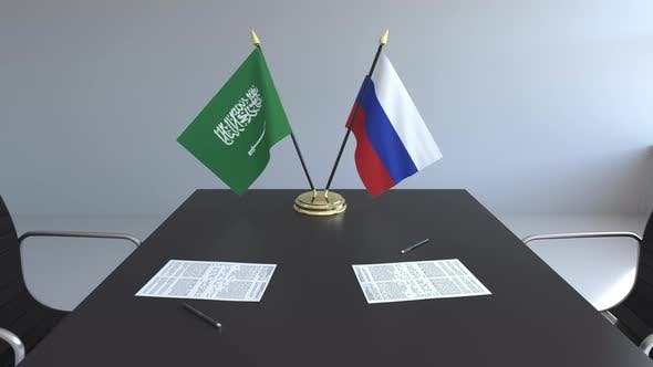 Flags of Saudi Arabia and Russia and Papers on the Table