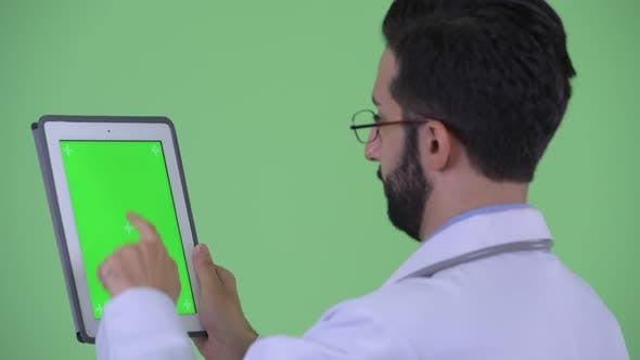 Thumbnail for Closeup Rear View of Happy Young Bearded Persian Man Doctor Using Digital Tablet