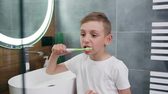 Boy Which Standing Near the Bathroom Mirror and Carefully Cleaning Teeth with Brush