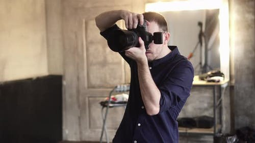 A Young Male Photographer Is Photographing a Model in the Studio.