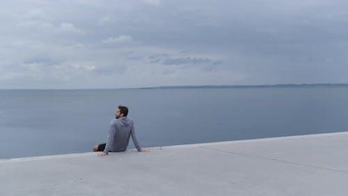 Athlete In Hoody Resting By Sea