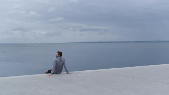 Thumbnail for Athlete In Hoody Resting By Sea