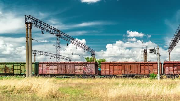 Cover Image for A Chain of Cargo Wagons on a Rail Road at the Background Blue Sky. June 2019 - Almaty, Nursultan