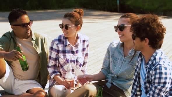 Friends Clinking Drinks on Wooden Terrace