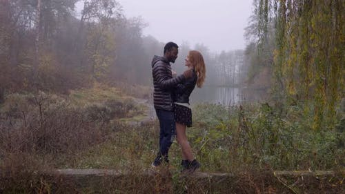 Interracial Love Concept. Beautiful Young Interracial Couple Posing in the Foggy Autumn Park
