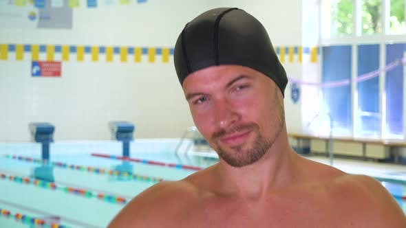 Thumbnail for A Professional Swimmer Takes Off His Goggles and Smiles at the Camera at an Indoor Pool - Closeup