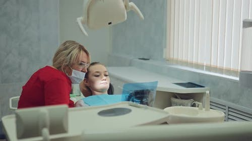Beautiful Female Dentist Looking at an Xray Picture with a Patient
