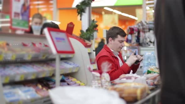 A Male Salesman a Cashier in a Supermarket Examines and Corrects His Medical Mask