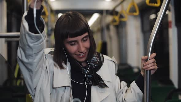 Thumbnail for Portrait of Young Woman Wearing in Coat with Headphones Listening To Music and Funny Dancing in