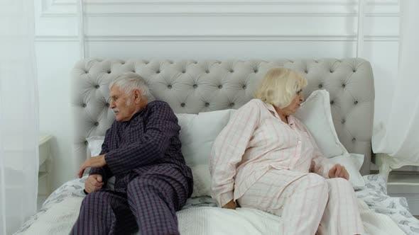 Thumbnail for Senior Elderly Couple in Pyjamas Lying on Bed Having an Argument in Bedroom, Grandparents Quarrel