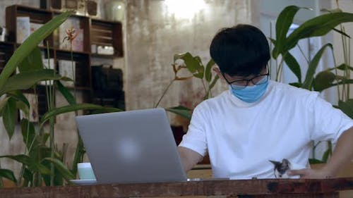 Young Man Teenage with Glasses. Male Teenager in Protective Mask, Student Working on Laptop From