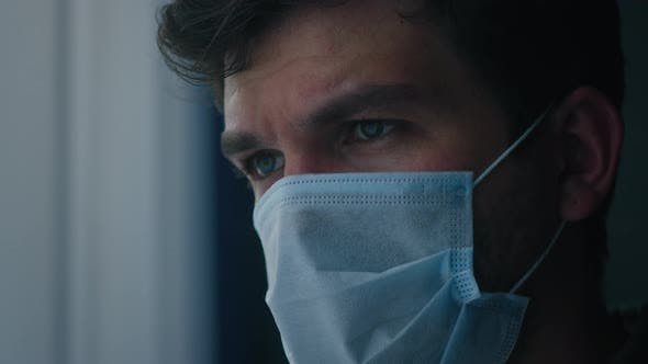Serious Man Wearing Protective Medical Mask on Face
