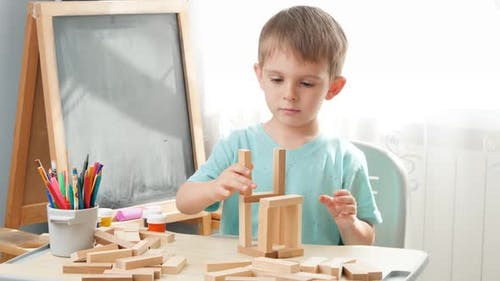 Portrait of Little Boy Playing with Wooden Toy Blocks and Building Tower From Bricks