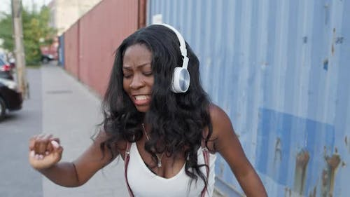 Walk Down The Street Of Young Black Girl. She Is In Headphones.