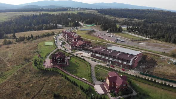 Drone is flying over biathlon sports base in green pine trees mountains