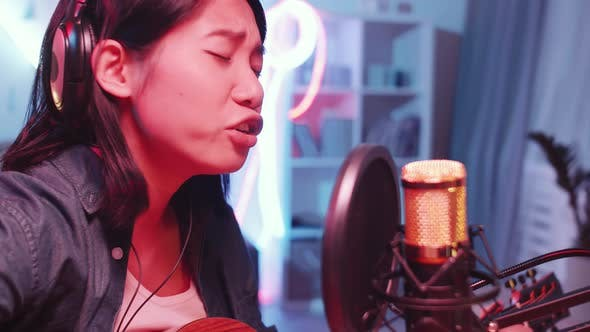 Thumbnail for Young Asian Woman Recording Song in Home Studio with Neon Light