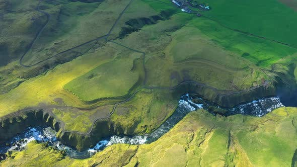 Aerial Flying Above the Vibrant Green Lava Hills and the River Skogar in Iceland