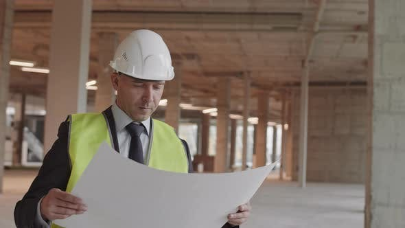 Caucasian Construction Supervisor Posing with Paper