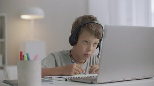 Boy with Headphones on Head and Laptop on Table Is Drawing at Home at Isolation Period at Pandemic