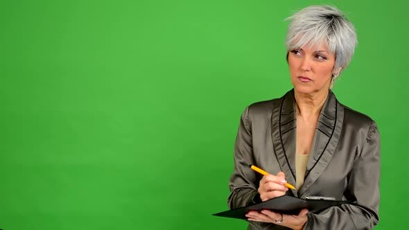 Thumbnail for Business Middle Aged Woman Writes To Paper (Serious Face) - Green Screen - Studio