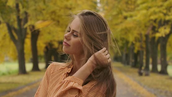 Thumbnail for Close-up Portrait of Cute Caucasian Girl Standing in Autumn Park and Sighing
