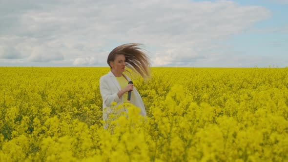 Thumbnail for A Mad Woman Singer with a Microphone in a Field of Rapeseed with Yellow Flowers Jumps Shakes Her