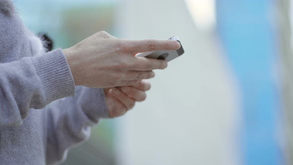 Female Hands Using Smartphone on Blurred Background