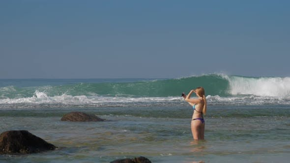 Thumbnail for Woman Holds Phone in Hands and Takes Photo of Waving Ocean