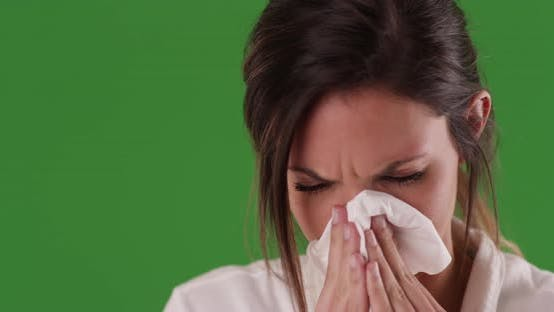 Thumbnail for Sick Caucasian woman blowing nose into paper tissue on greenscreen