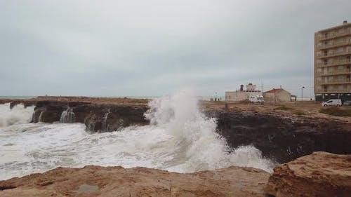 Zeitlupe Aufnahmen von Wellen, die heftig gegen Felsen stürzen