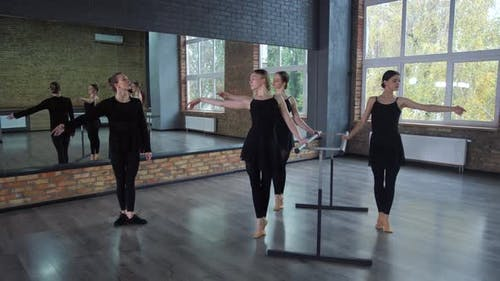 Young Ballerinas Practicing at Ballet Barre